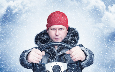 Frozen man in winter clothes drives a car in a snowstorm with his hands on the steering wheel. Front view
