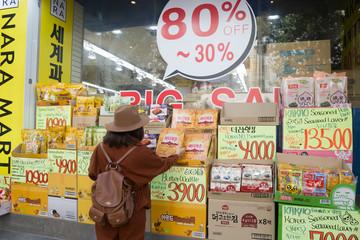 Seoul, South Korea November 7, 2019 A tourist woman is selecting snacks for souvenir at the big shop in Hong Dae Market, Seoul, Korea.