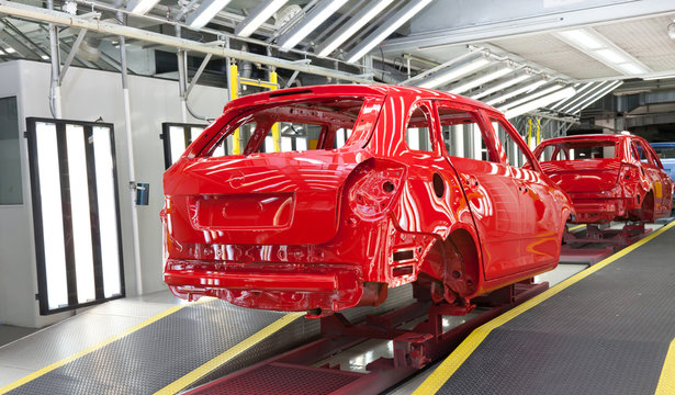 red car body at quality check after on assembly line after paintshop at car manufacture