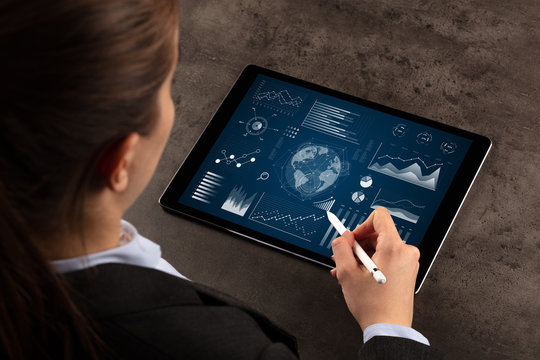 Business woman verifying reports on tablet with pencil in business suit