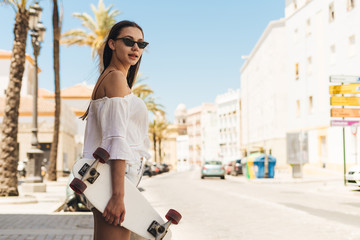 spa girl in a southern city in white clothes, among white houses. in her hand is a skate board