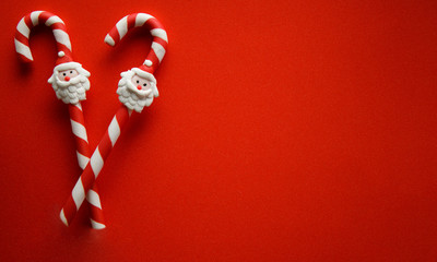 Christmas candy cane with Santa Claus ornament on red background