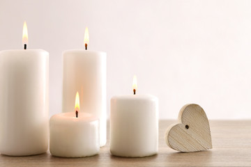 Background with burning candles and heart on wooden table