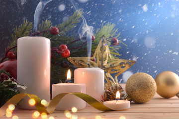 Burning and extinguished candles on Christmas table snowing at night