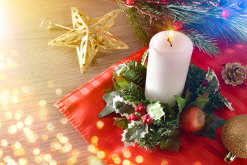 Candle on Christmas table with floral arrangement with lights