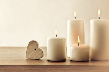 Vintage background with burning candles and heart on wooden table