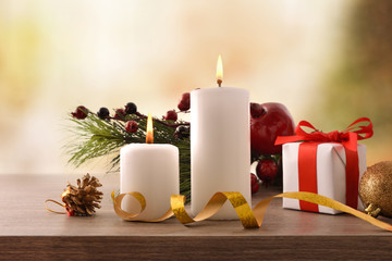 Two burning candles on Christmas wooden table with gift front