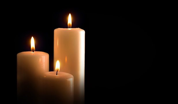Three burning candles isolated black front view