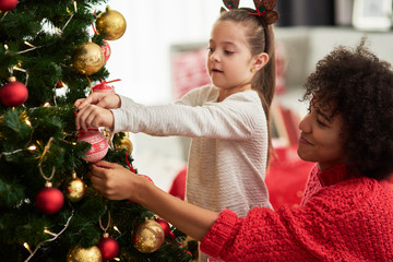 Charming girl and mom decorating Christmas tree