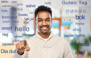 choice, gesture and people concept - smiling indian man pointing finger to camera at office over...