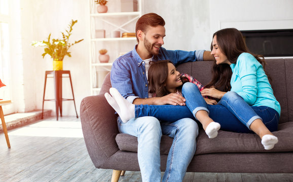 Happy childhood. A beautiful family of father, daughter and mom are sitting on the sofa at home, laughing, hugging and playing with each other.