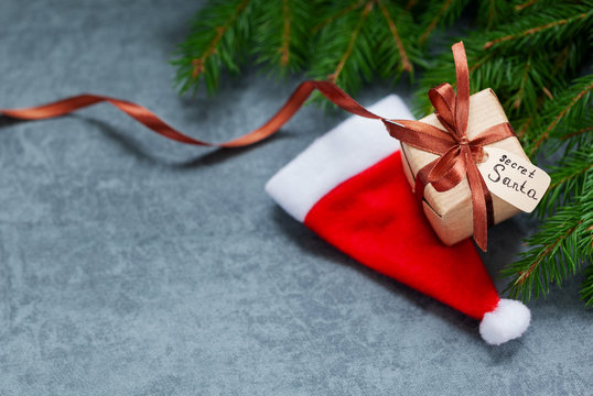 Christmas present or box with tag secret santa with Santa hat on dark background.