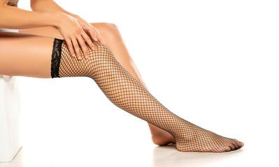 Woman wearing black fish net nylon socks on white background