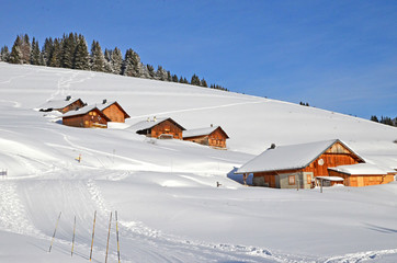 Beautiful peaceful winter landscape in the Frence Alps, at one of the ski stations, France. Several typical wooden houses (called chalet in French).