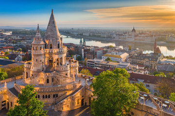 Photo sur Toile Budapest Budapest, Hungary - Beautiful golden summer sunrise with the tower of Fisherman's Bastion and green trees. Parliament of Hungary and River Danube at background. Blue sky.