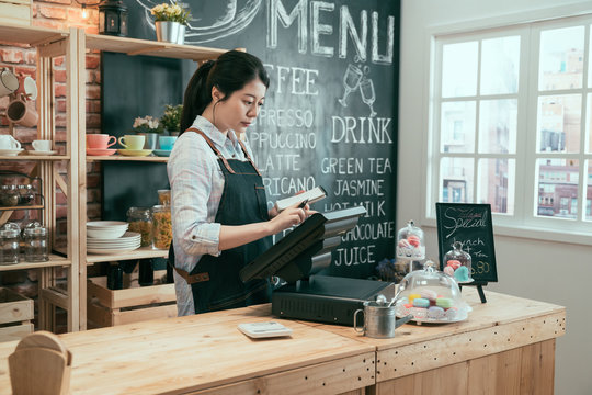 Young asian japanese lady waitress using digital device for payment in coffee shop counter. beautiful woman staff enter customer order from note into point of sale terminal machine in cafe store.