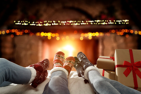 Blurred background of chrsitmas fireplace.Orange color of warm light of fire.Woman legs with socks and jeans.Copy space.Free place for your decoration.Cold winter december night.Christmas Eve party.