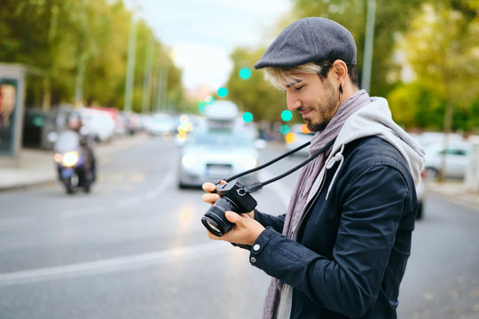 Hipster Street Photographer Reviewing Pictures On Mirrorless Camera Display