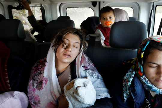 Migrants from Afghanistan board a minibus following a rescue operation by Frontex, at the port of Skala Sikamias, on the island of Lesbos