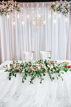 Wedding presidium in restaurant, copy space. Banquet table for newlyweds with flowers, greenery, candles and garland ligths. Lush floral arrangement. Luxury wedding decorations