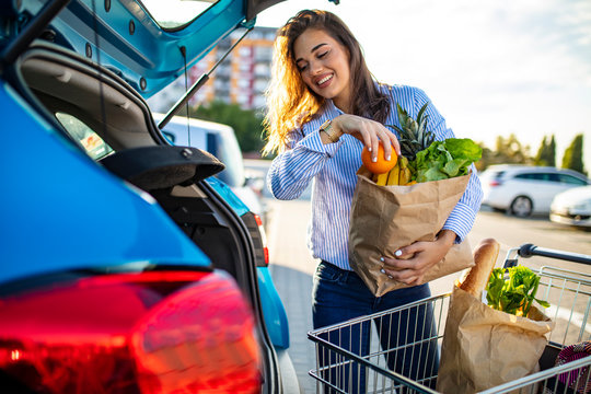 Young woman with groceries at parking lot. Young women packing groceries from supermarket in car trunk. Happy young woman holding groceries in reusable bag