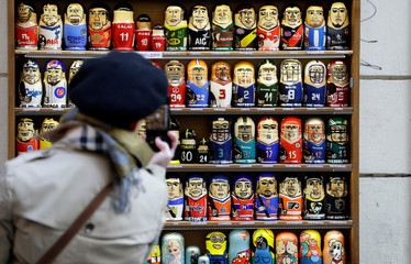 A tourist takes a picture of Matryoshka wooden dolls outside of a souvenir shop in Prague