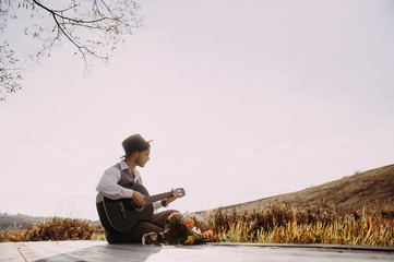 Young man playing guitar sitting on the bank of a mountain river on a background of rocks and forest. Handsome hippie style guitarist engrossed on music outdoors. Concept of freedom relaxation. Place