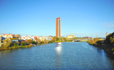 River Guadalquivir and the neighborhood of Triana with the Pelli Tower skyscraper in the background. Seville Andalusia Spain