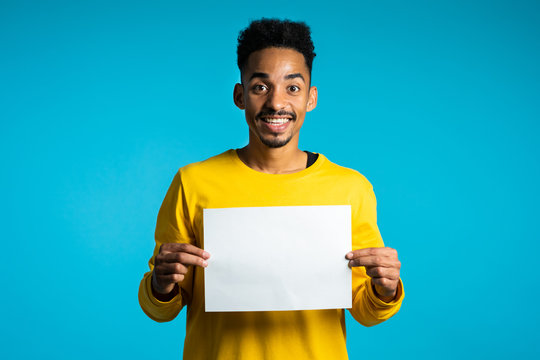 Portrait of young handsome african american man holding white empty paper blank on blue studio background. Copy space. Positive guy with sign