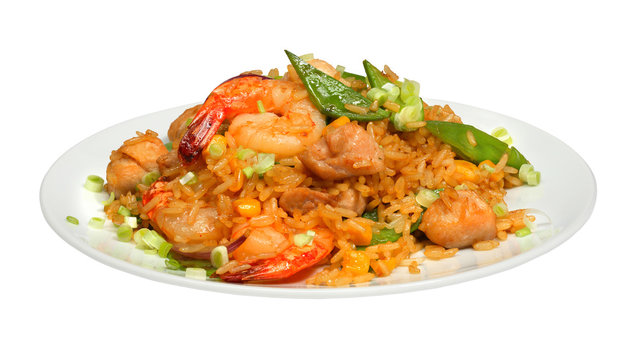 Rice with chicken meat, shrimps and vegetables on white round plate