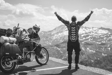 A back view motorcycle traveler is happy arrived at his destination. Conquering the top of the mountain, Grossglockner pass, biker dressed in a protective jacket armor black and white. Austria Fototapete