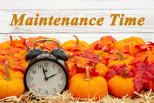 Maintenance Time message with a retro alarm clock with pumpkins and fall leaves