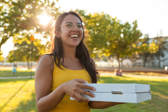 Happy joyful young woman carrying pizza for picnic in park. Beautiful woman standing outdoors, holding pizza boxes, looking away, laughing. Food delivery concept