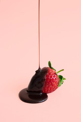 Minimal dark chocolate pouring drop to red strawberries on pastel pink background