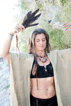 Soul Retrieval shaman woman with feather wand and sage smudge.