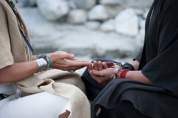 Modern shamanic healer utilizing ancient technologies. Man and woman shaman sharing symbolic offering and receiving of  traditional corn.