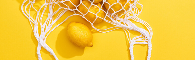 top view of fresh ripe whole lemons in eco string bag on yellow background, panoramic shot