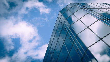 Futuristic Business. Low angle view of a glass and steel skyscraper blending into and reflecting the blue sky and clouds. Fotobehang