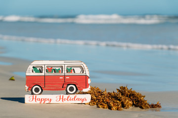 Christmas in Florida concept. Happy Holidays VW bus sign on the shores of New Smyrna Beach, Florida