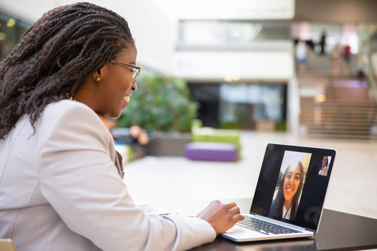 Happy female office friends talking through video call. Business women using digital devices for video chat. Internet connection concept