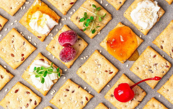 Homemade freshly baked crackers with flax and sesame seeds with various serving options are laid out on baking paper, top view. Crackers with seeds, ricotta, jam, berries and microgreens, flat lay.