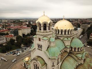 Vue aérienne d'une immense cathédrale avec dômes dorés et verts et croix en or sur le toit, sur une place urbaine avec ville en fond et ciel gris