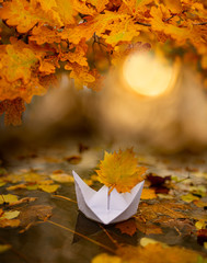 white paper boat on an autumn river close up