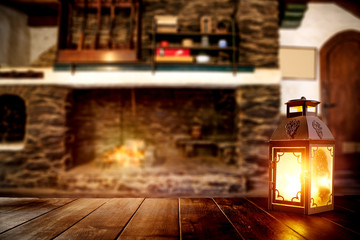 Brown old wooden table with chrsitmas lamp and natural fire.Blurred background of interior of the...