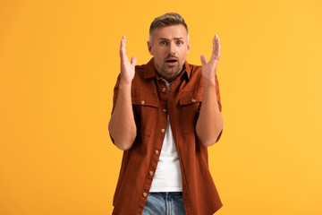 shocked man gesturing while looking at camera isolated on orange