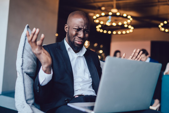 Frowning dissatisfied businessman watching laptop