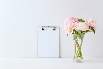 Mockup with a clipboard and pink peonies in a vase on a white background