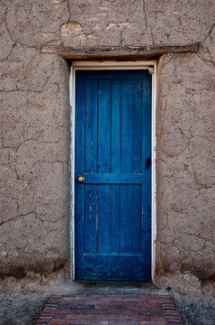 Old blue door traditional adobe building in New Mexico USA.