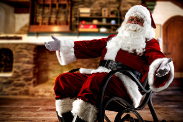 Red old Santa Claus in rocking chair.Fireplace in home interior.Copy space.Free space for your decoration.Dark mood photo of home interior.Xmas time and cold december night.