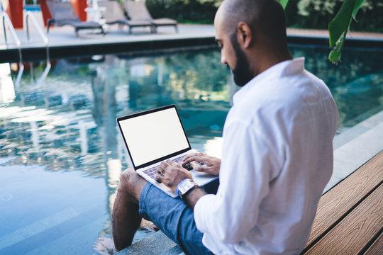 Man working on laptop sitting near pool